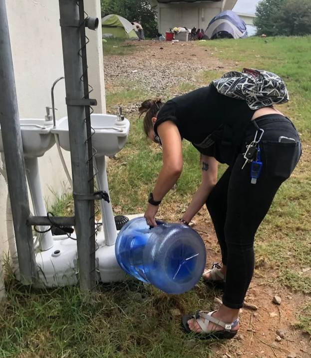 Author April Ballard refilling water at a Love Beyond Walls handwashing station for people experiencing homelessness residing in an encampment in Atlanta, Georgia Alison Hoover