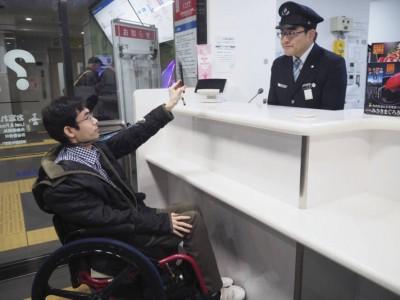 A man in a wheelchair presenting his credentials to an airport official