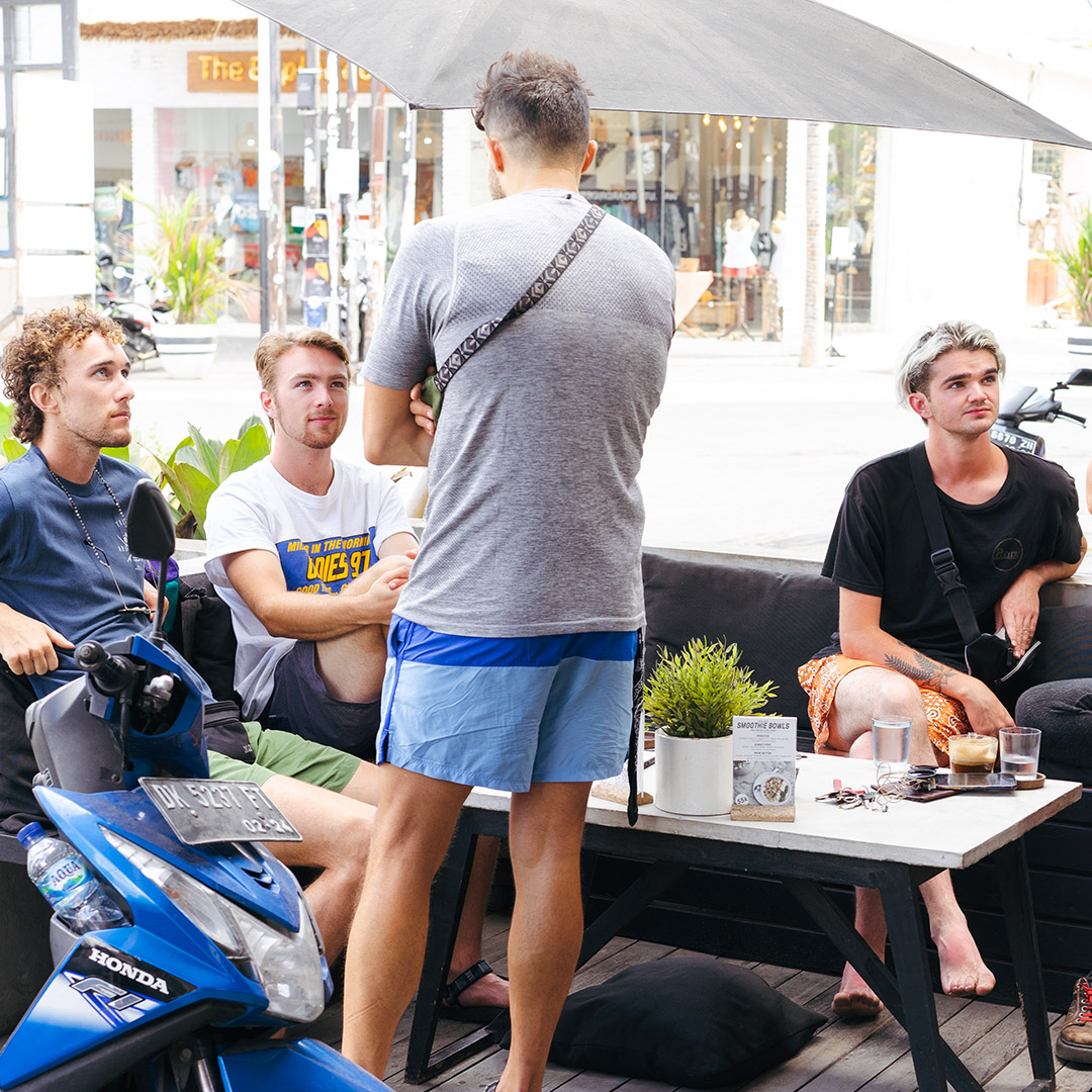 four guys sitting in bgs coffee bar outdoor seating