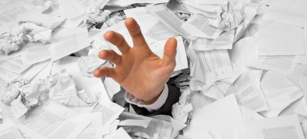 Hand reaches out from crumpled papers
