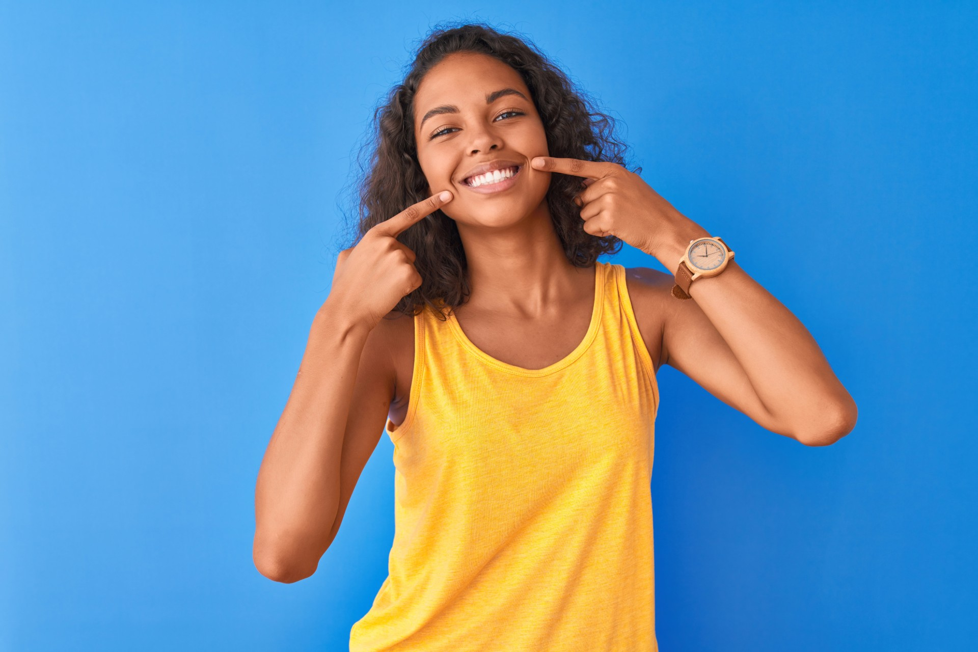 Girl standing against a blue wall, while showing off her new smile.