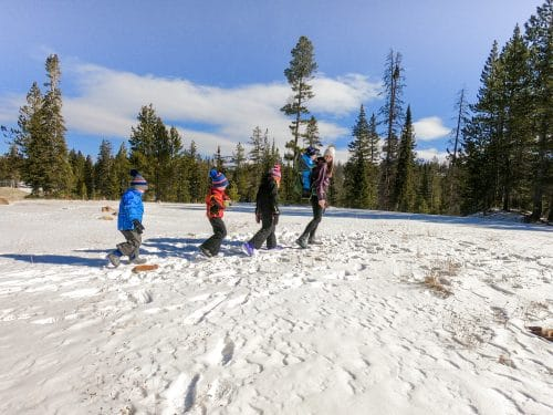 family hiking in the snow with boots on