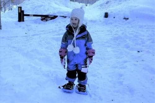 little kid in snowsuit in winter with snow
