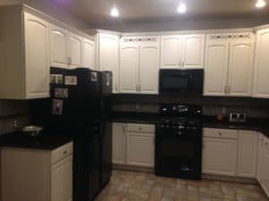 White painted cabinets around fridge and hanging microwave