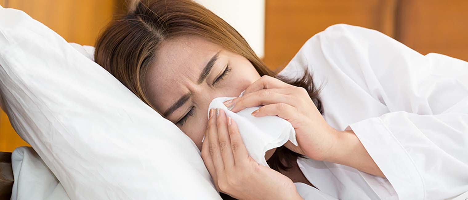 sick woman blowing her nose in bed