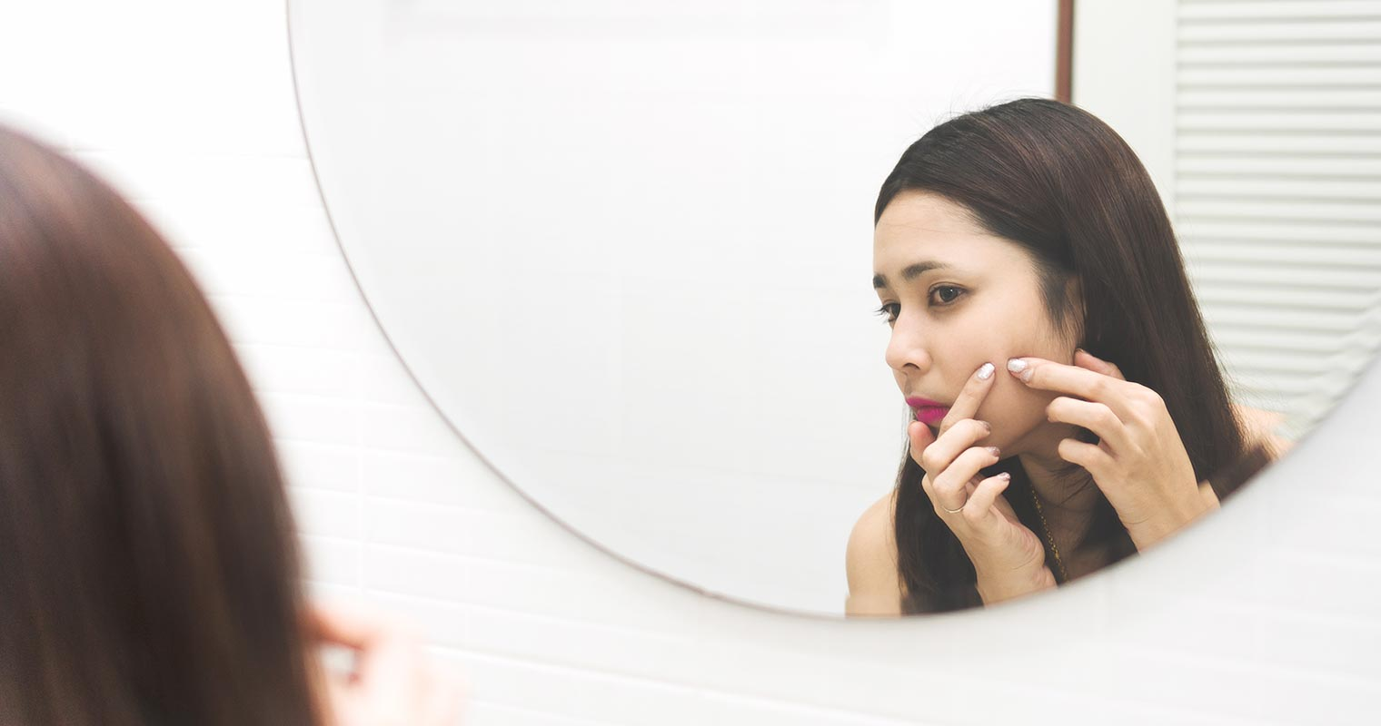 girl squeezing pimple in front of a mirror