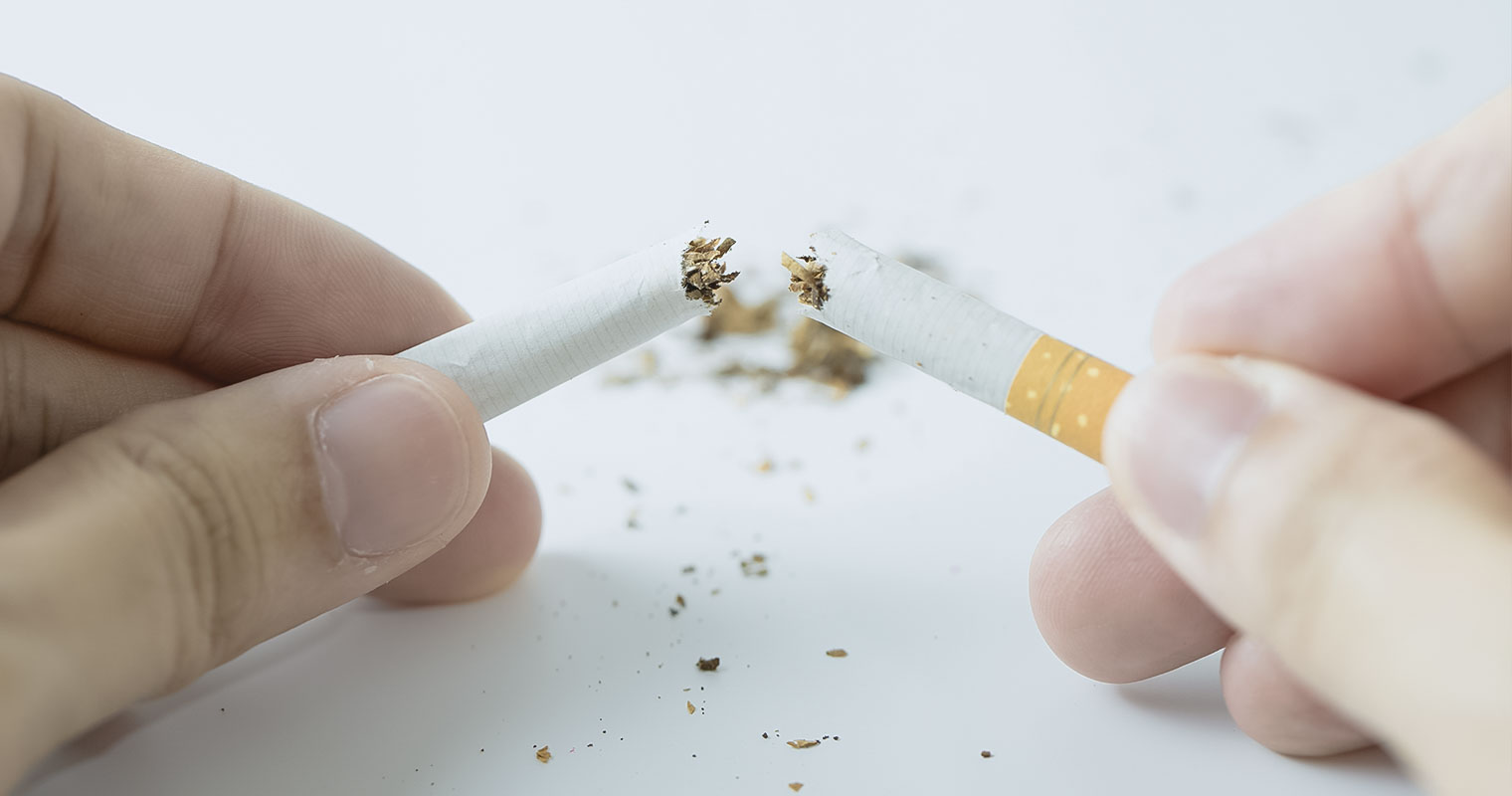 Breaking apart a piece of cigarette to expose the tobacco