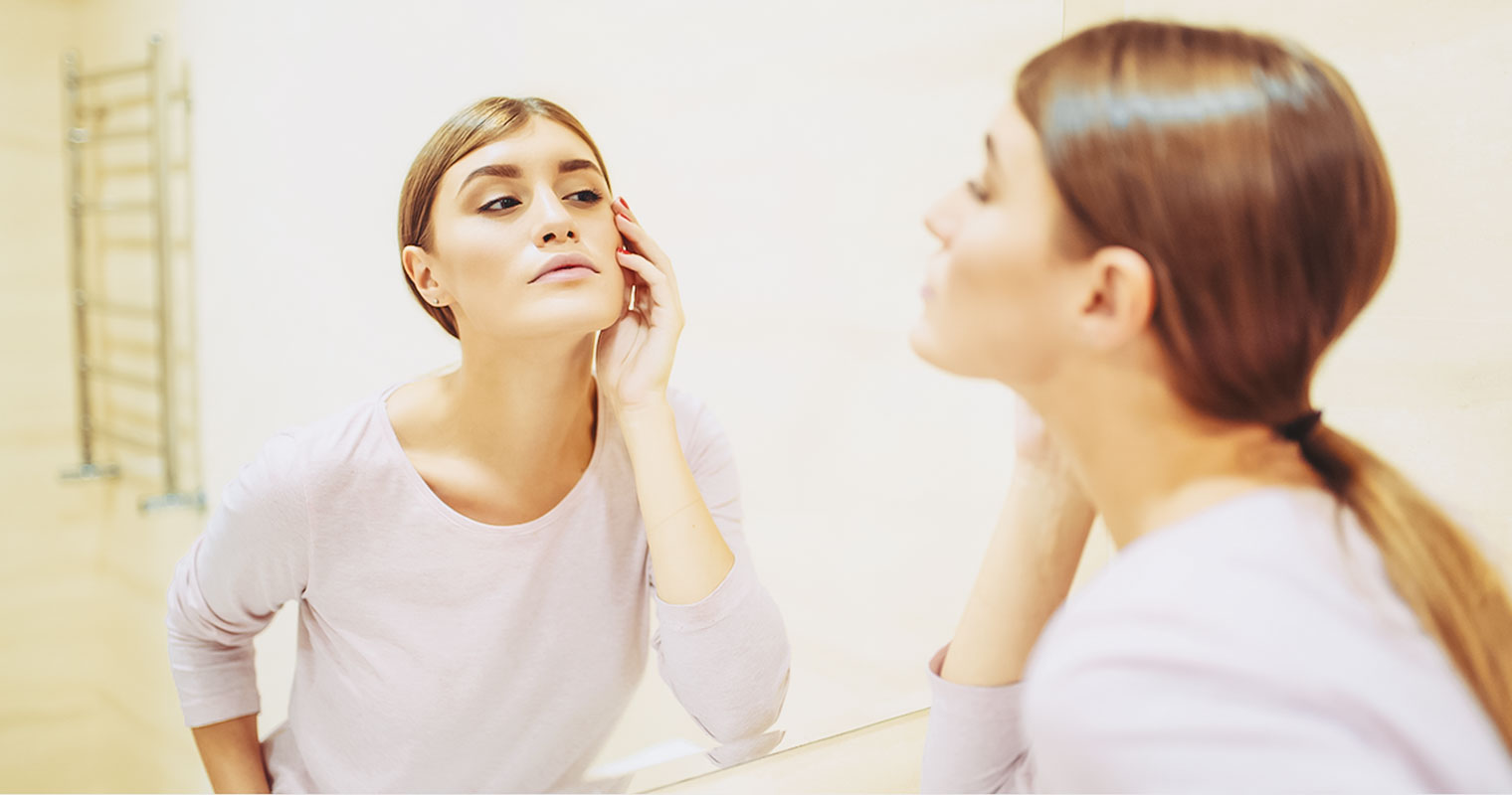 Woman checking her ACNE in a mirror