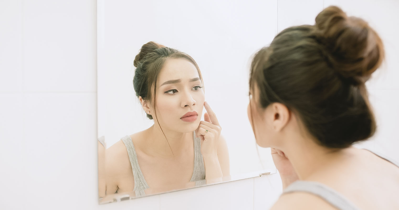 young woman looking to mirror at home bathroom looking worried