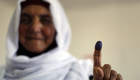 A Palestinian woman shows her ink-stained finger after casting her ballot for municipal elections at a polling station in the West Bank village of Shiyoukh