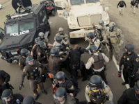Over 300 police officers in riot gear, eight ATVs, five armored vehicles, two helicopters, and military humvees showed up north of the treaty camp just east of Highway 1806. Photo by Jonathan Klett