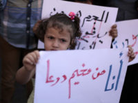 """""""I am from Deraa camp"""" reads a sign held by a girl during a demonstration outside UNRWA's Gaza City headquarters in October 2013./ Ashraf Amra APA images"""