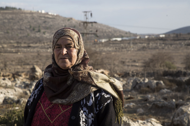 Maryam Hamad, from the West Bank village of Silwad, is pictured with the Israeli Ofra settlement in the background. She is one of the landowners on whose land the nearby Amona outpost was built. According to an Israeli high court decision, the settlers must evacuate this month.  Photo/Keren Manor/ ActiveStills