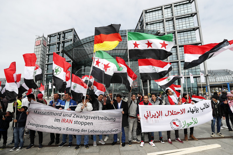 epa05919708 Demonstrators hold flags of the region of Al-Ahwaz and Syria as they take part in a rally in support of the Ahwazi minority in Iran, in Berlin, Germany, 21 April 2017. Dozens of demonstrators took part in the march striving for the recognition of this minority and their human rights. The Ahwazi live within the Iranian province of Khuzestan and constitute an ethnic, linguistic and cultural minority in Iran.  EPA/FELIPE TRUEBA