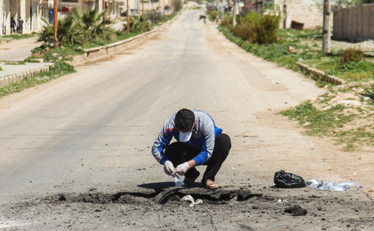 A Syrian man collects samples from the site of a suspected toxic gas attack in Khan Sheikhun, in Syria's northwestern Idlib province, on April 5, 2017. International outrage is mounting over a suspected chemical attack that killed scores of civilians in Khan Sheikhun on April 4, 2017. / AFP PHOTO / Omar haj kadour
