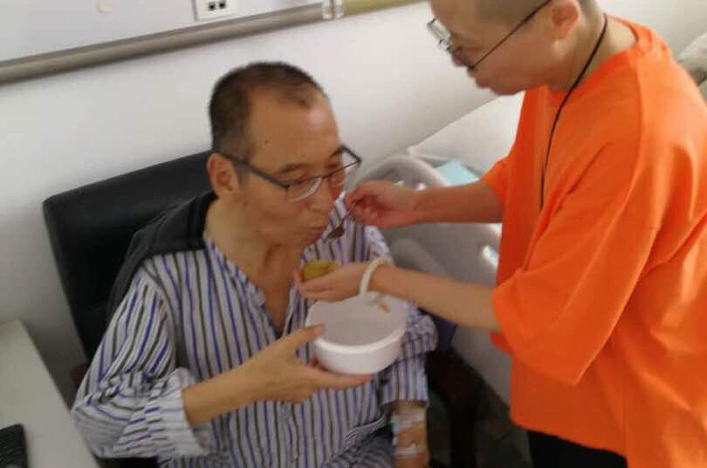 In this undated photo, Liu Xia feeds her husband Liu Xiaobo at a hospital in China.