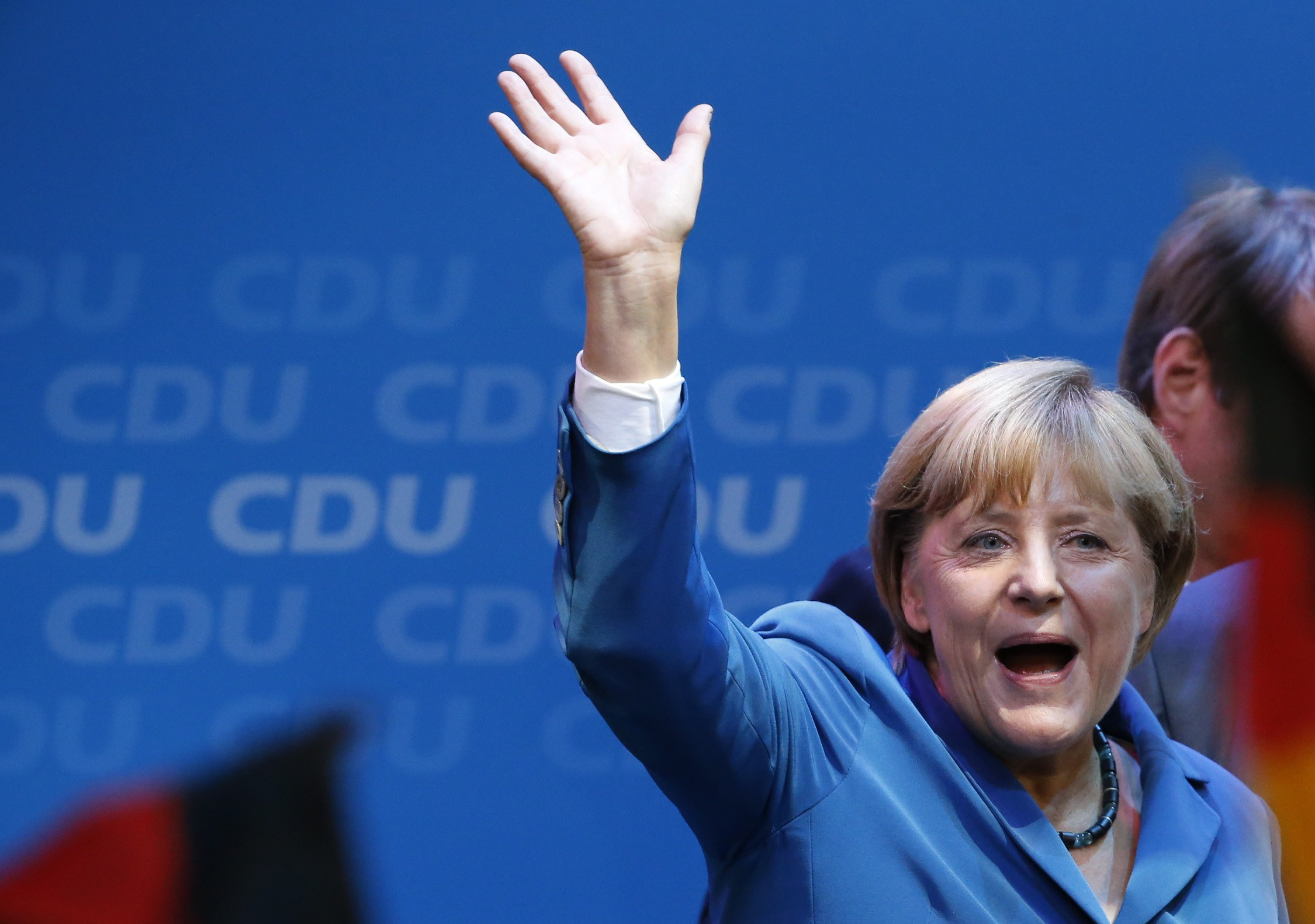 German Chancellor and leader of the Christian Democratic Union (CDU) Angela Merkel waves to supporters as she celebrates with party members after first exit polls in the German general election (Bundestagswahl) at the CDU party headquarters in Berlin September 22, 2013. Chancellor Angela Merkel won a landslide personal victory in a German election on Sunday, putting her within reach of the first absolute majority in parliament in half a century, a ringing endorsement of her steady leadership in the euro crisis.                REUTERS/Fabrizio Bensch (GERMANY  - Tags: POLITICS ELECTIONS)