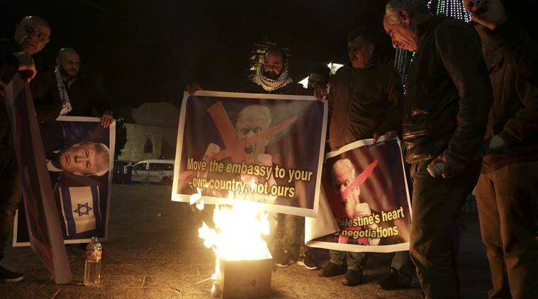Palestinian burn a poster of the U.S. President Donald Trump during a protest in Bethlehem, West Bank, Tuesday, Dec. 6, 2017. President Trump forged ahead Tuesday with plans to recognize Jerusalem as Israel's capital despite intense Arab, Muslim and European opposition to a move that would upend decades of U.S. policy and risk potentially violent protests. (AP Photo/Mahmoud Illean)