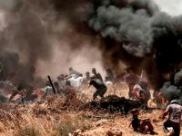 TOPSHOT - Palestinians clash with with Israeli forces near the border between the Gaza strip and Israel east of Gaza City on May 14, 2018, as Palestinians protest over the inauguration of the US embassy following its controversial move to Jerusalem. - Dozens of Palestinians were killed by Israeli fire on May 14 as tens of thousands protested and clashes erupted along the Gaza border against the US transfer of its embassy to Jerusalem, after months of global outcry, Palestinian anger and exuberant praise from Israelis over President Donald Trump's decision tossing aside decades of precedent. (Photo by MAHMUD HAMS / AFP)        (Photo credit should read MAHMUD HAMS/AFP/Getty Images)
