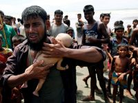 Ahmed, a Rohingya refugee man cries as he holds his 40-day-old son, who died as a boat capsized in the shore of Shah Porir Dwip while crossing ...
