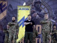 "The Azov Battalion uses the Nazi Wolfsangel symbol as its logo. Its founder Andriy Biletsky (center) has moved to ban ""race mixing"" in the Ukranian parliament. (Azov/Twitter)"