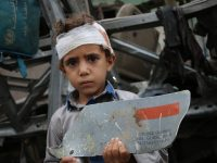 A young survivor of August 9 Saudi-led attack on his school bus, with fragment of U.S. made missile - Photo/Ahmad Algohbarya