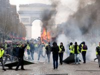 PARIS, FRANCE - NOVEMBER 24: A fire rages as protesters wearing yellow vests protest against rising fuel prices on the Champs-Elysees avenue on November 24, 2018 in Paris France. The police have used tear gas and water cannon to in an attempt to disperse the protest, which was organised by 'Yellow Vests' (Vestes Jaunes), a protest movement without political affiliation that protests against taxes and rising fuel prices. (Photo by Chesnot/Getty Images)