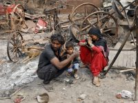 A woman sitting with her husband and their child reacts next to damaged property after their house was burnt by a mob on Tuesday in a riot affected area after clashes erupted between people demonstrating for and against a new citizenship law in New Delhi, India, February 28, 2020. REUTERS/Adnan Abidi - RC2L9F9XG1SM