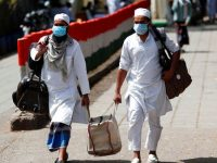 Men wearing protective masks walk as they carry bags, amid concerns about the spread of coronavirus disease (COVID-19), in Nizamuddin, area of New Delhi, India, March 31,  2020. REUTERS/Adnan Abidi