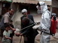 Sanaa, Yemen. 30th Apr, 2020. A health worker wearing a protective suit sprays disinfectant on the hands of people at a market in the old city of Sanaa, amid concerns of the spread of the coronavirus (COVID-19). Photo Credit: Hani Al-Ansi/dpa/Alamy Live News.