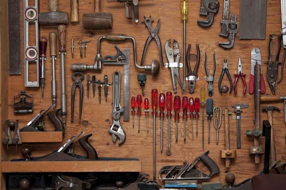 Database Administration: One Toolrtment of do it yourself tools hanging in a wooden cupboard against a wall [shutterstock: 55814938, Daleen Loest]