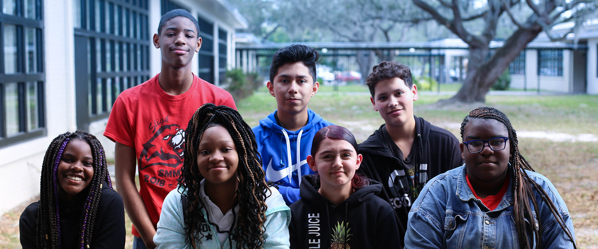 Group of 7 students standing outside in school courtyard, four people in front, three people standing behind, Hillsborough Education Foundation
