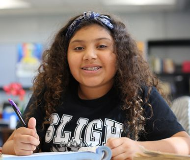 Donate school supplies, young girl in classroom, writing on desk, Hillsborough Education Foundation