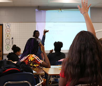 Students raising their hands in a classroom