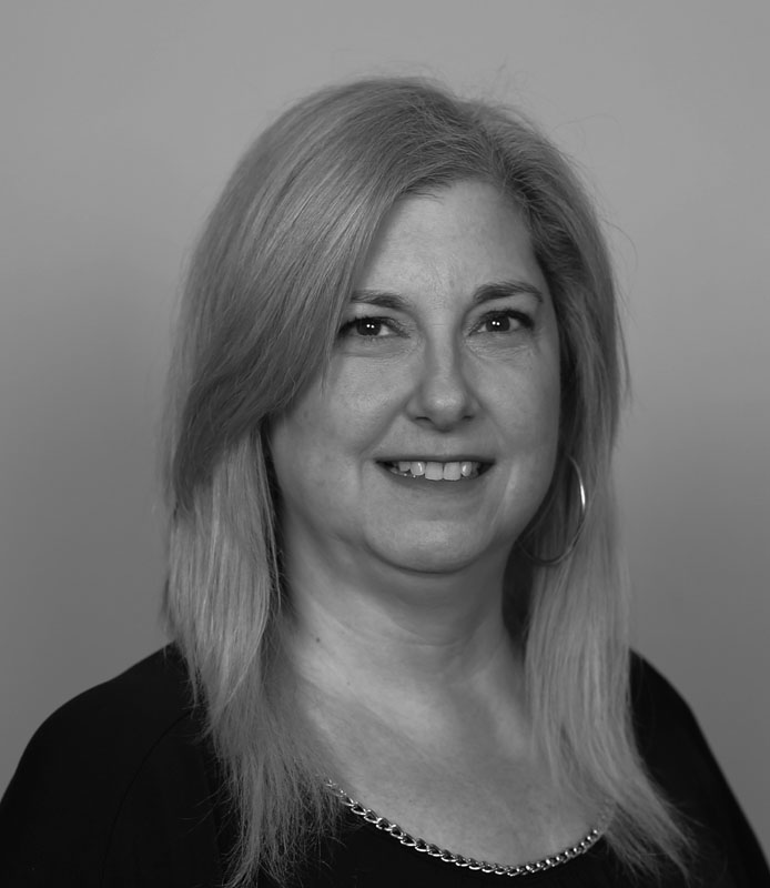 Laura Grucza, older woman with hoop earrings and blonde hair, black and white headshot, Hillsborough Education Foundation