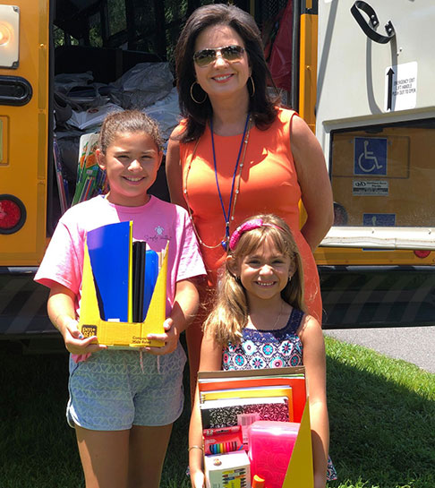 Mother and children showing school supplies collected for the Hillsborough Education Foundation