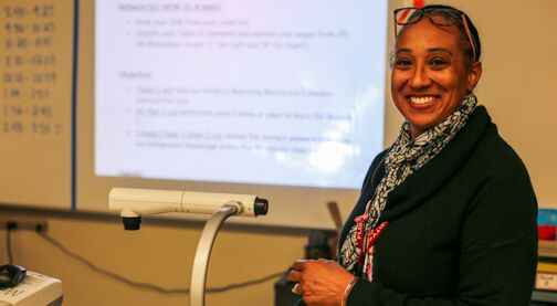 Support a teacher's classroom, teacher smiling in front of whiteboard, Hillsborough Education Foundation