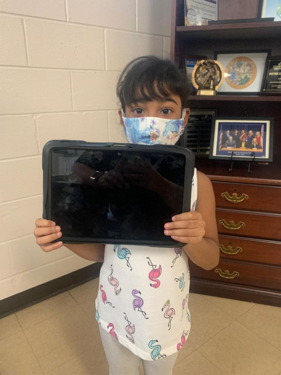 Student holding tablet provided by Hillsborough Education Foundation for summer learning