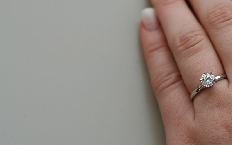 800px-Diamond_engagement_ring_on_woman_hand_6313