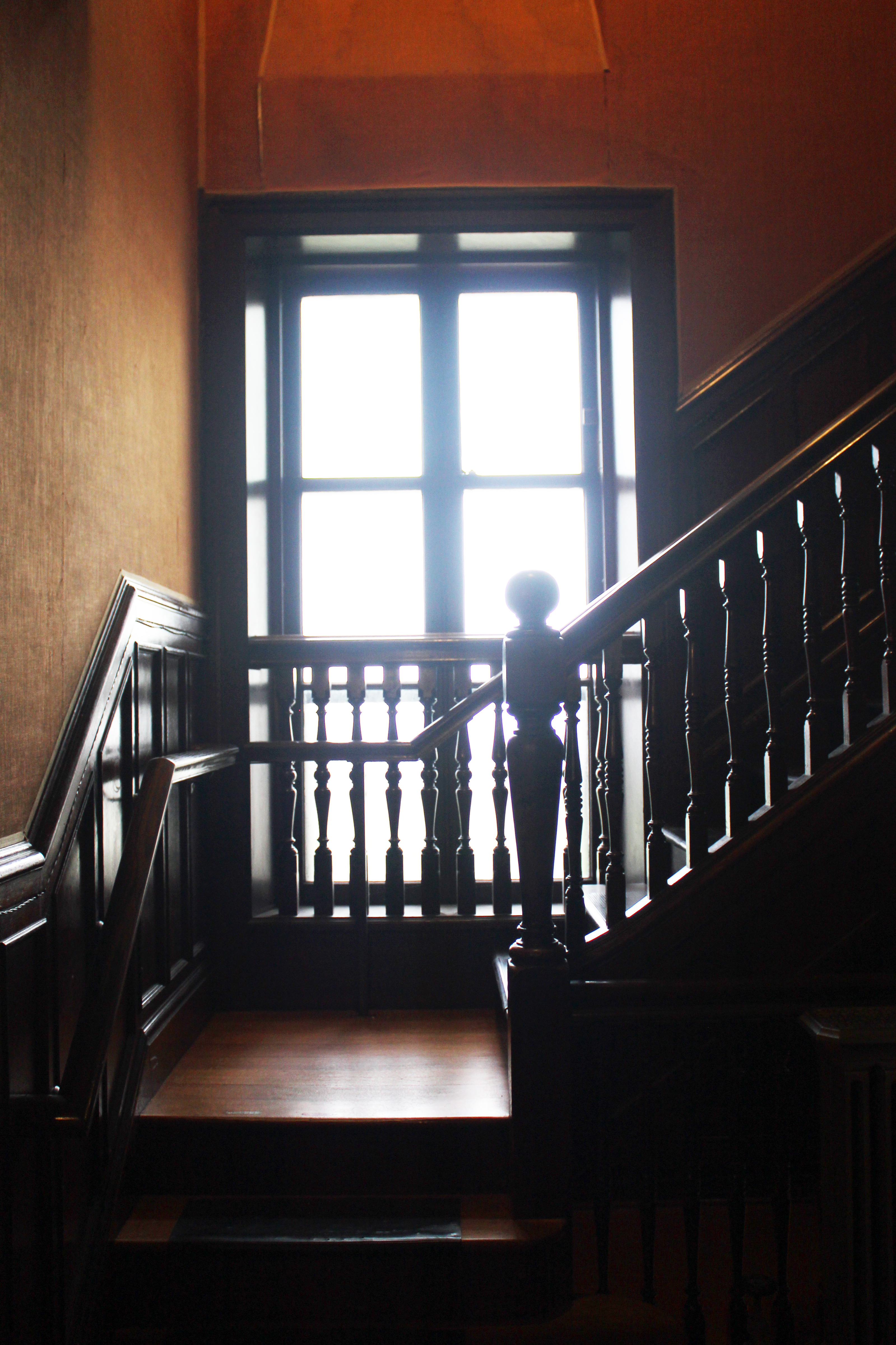 The Breakers - Newport RI | Diffused light pours through grand windows of the hallway leading into the kitchen of The Breakers. One assumes this area was frequented by staff alone, but with such exquisite woodwork and turned rails, who would mind?