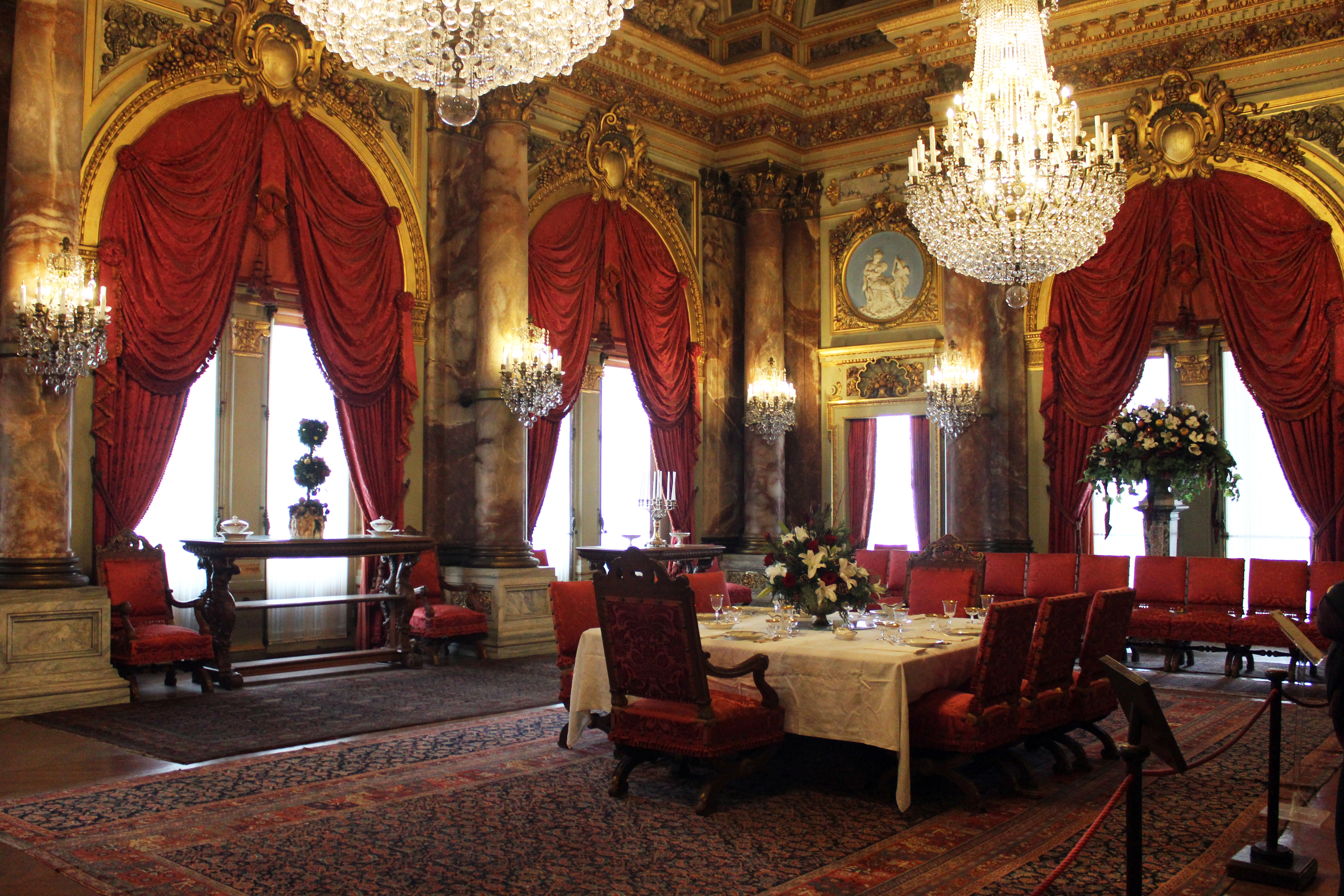 The Breakers - Newport RI | The Dining Room of The Breakers features twelve Corinthian columns, 18-, 22-, and 24-karat gilded walls, and an elaborate ceiling fresco. Two baccarat crystal chandeliers shimmer from above. Surely more than a few elite and famous guests have dined in the opulence of this majestic room.