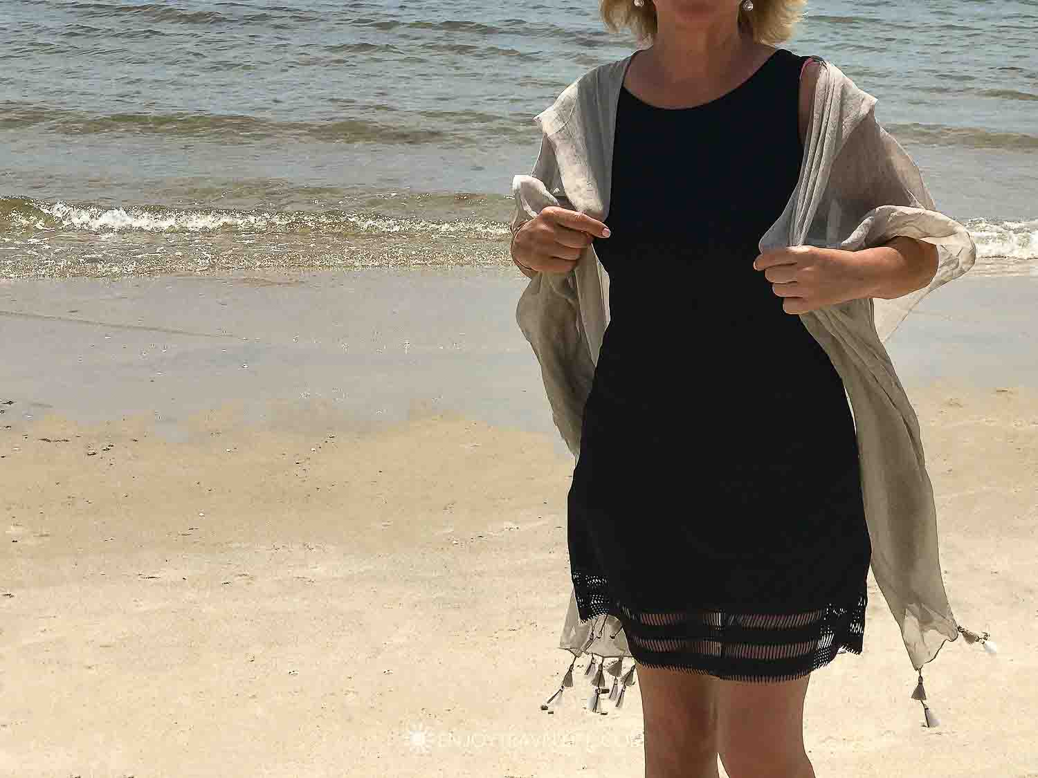 Taupe sarong wrap with tassels worn over black dress