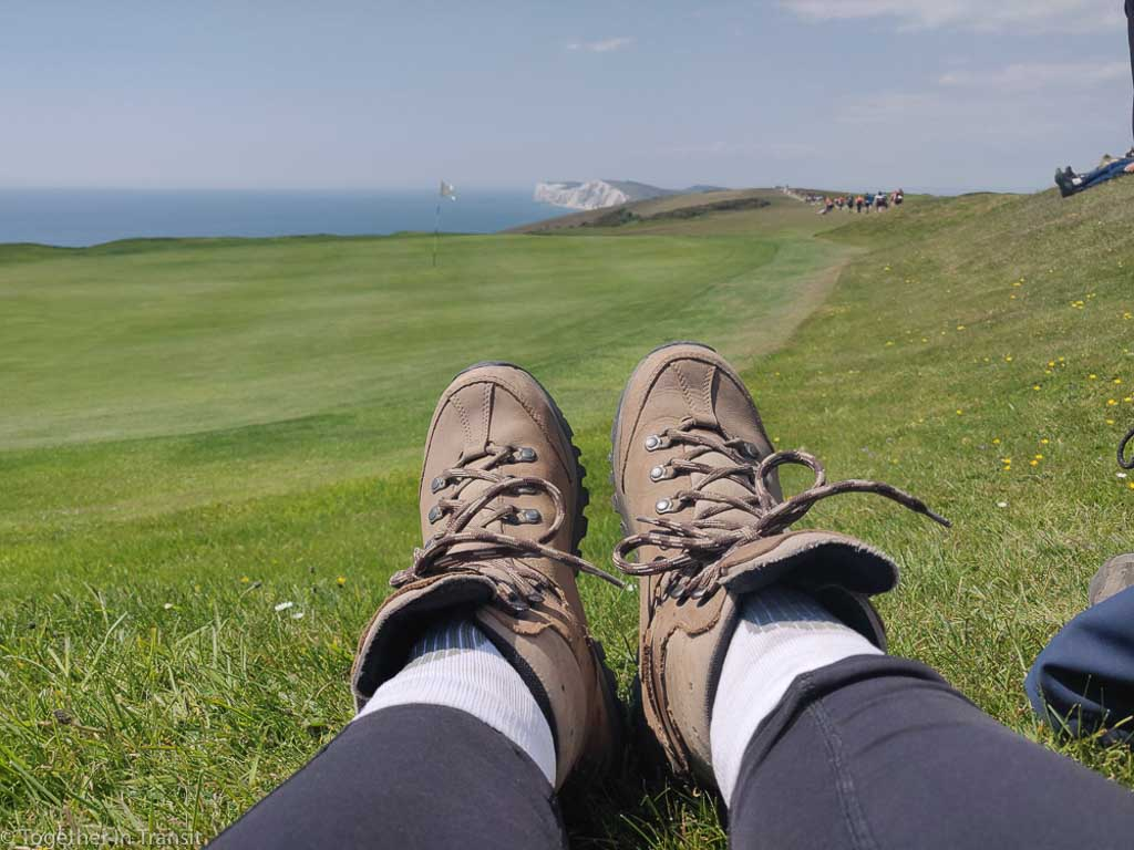 Person wearing hiking shoes and sitting in grass on The Isle of Wight, viewing the field, ocean, and cliffs.