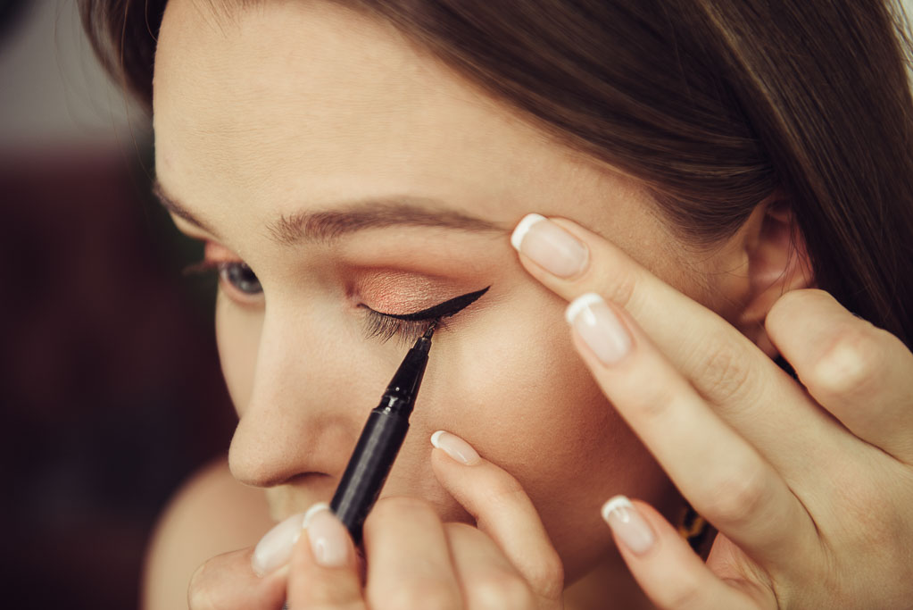 Travel beauty tips - woman applies eyeliner