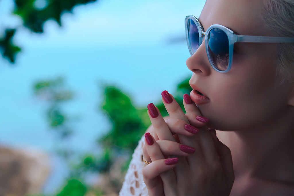 Travel beauty tips for women - woman in sunglasses with long-wearing nail polish