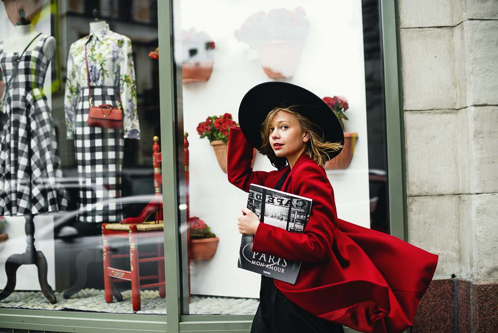Girl in red coat carrying travel magazine