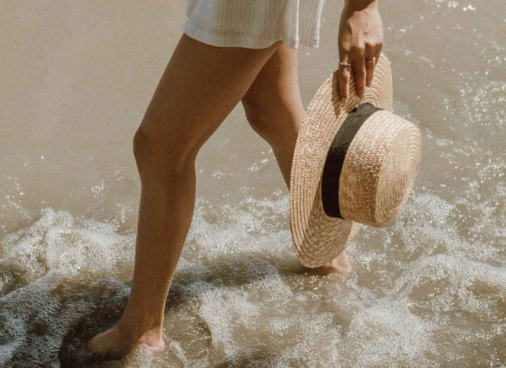 Woman walking in water carrying a straw hat