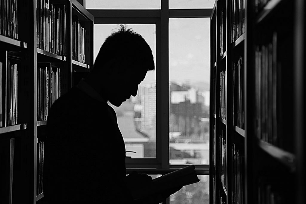 College student looks at a book in campus library overlooking the city