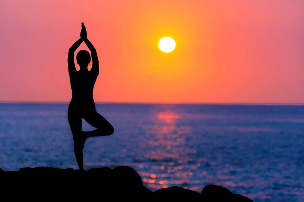 Woman practices yoga by the beach at sunset