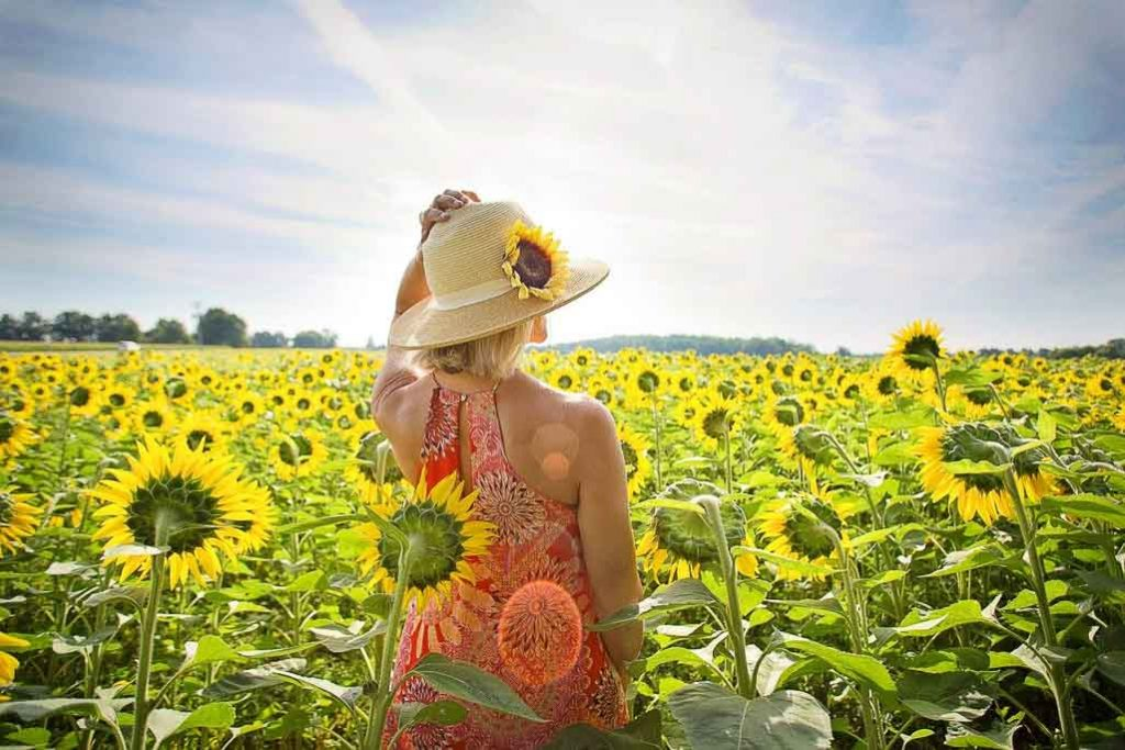 Inspirational Garden Quotes - woman with hat in field of sunflowers